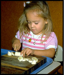 child cutting a banana